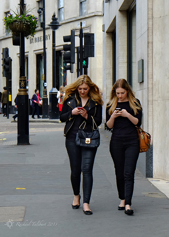 Two girls texting as they walk in Belgravia